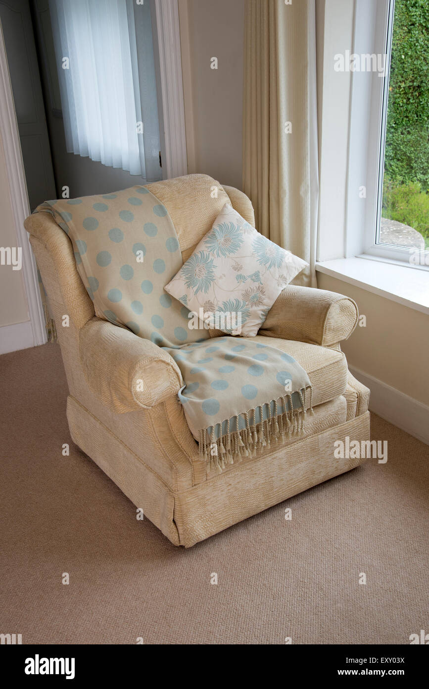 A comfortable easy chair with cushion and shawl - Stock Image