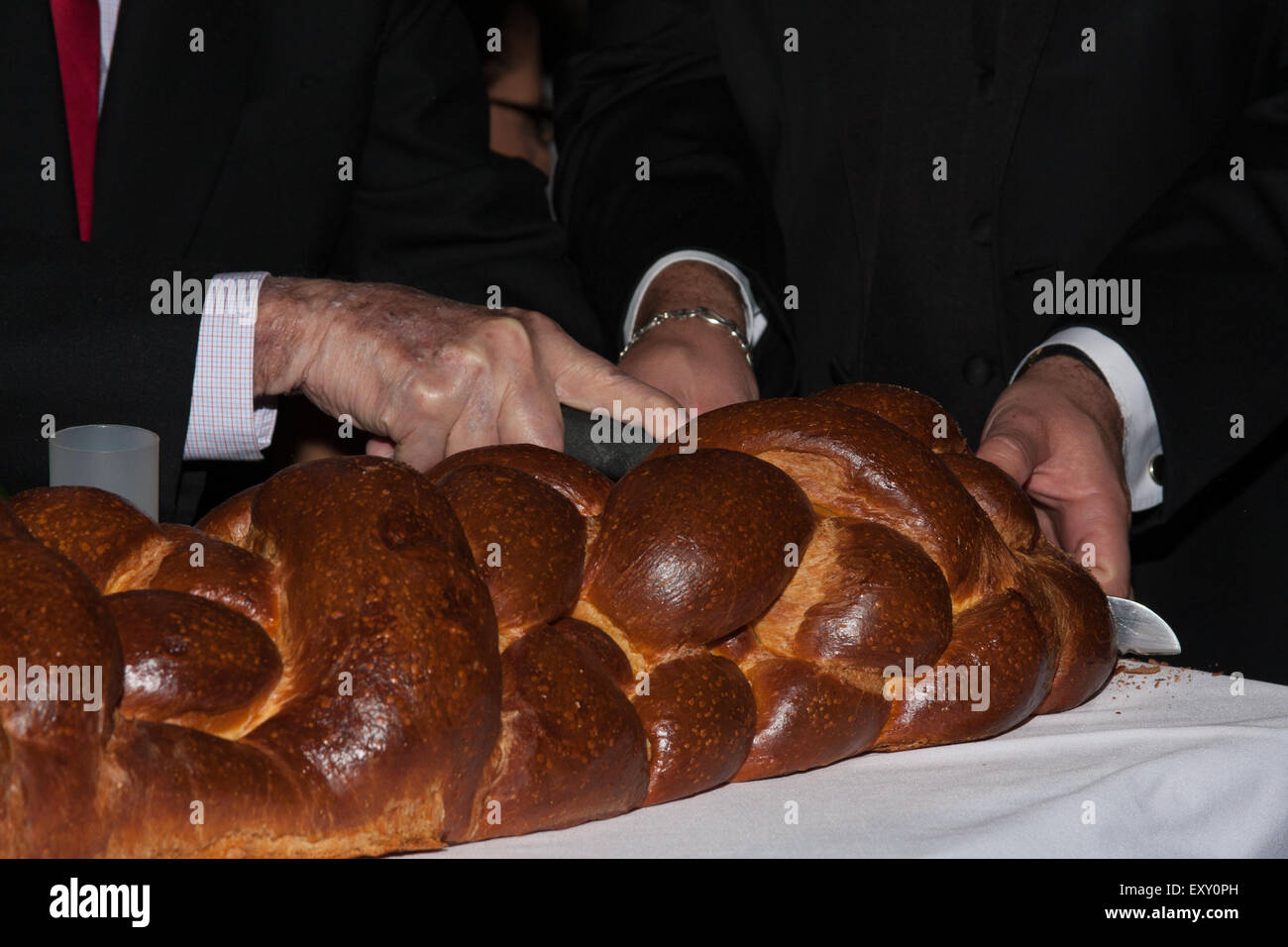 A grandfather cutting a challah bread at a bar mitzvah. - Stock Image
