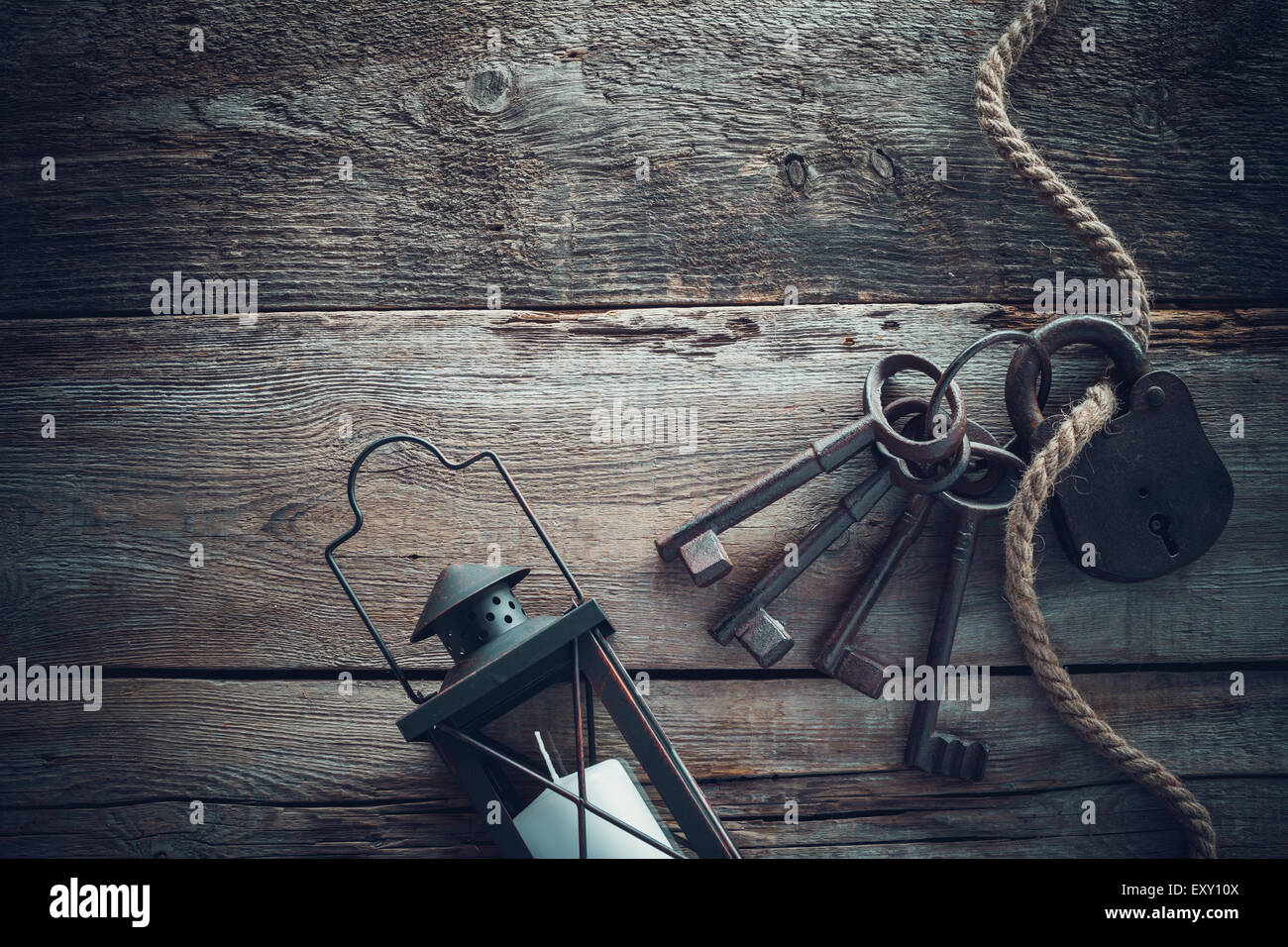 Old rusty lock with keys, vintage lamp and rope on wooden board. Top view. Retro stylized photo. - Stock Image