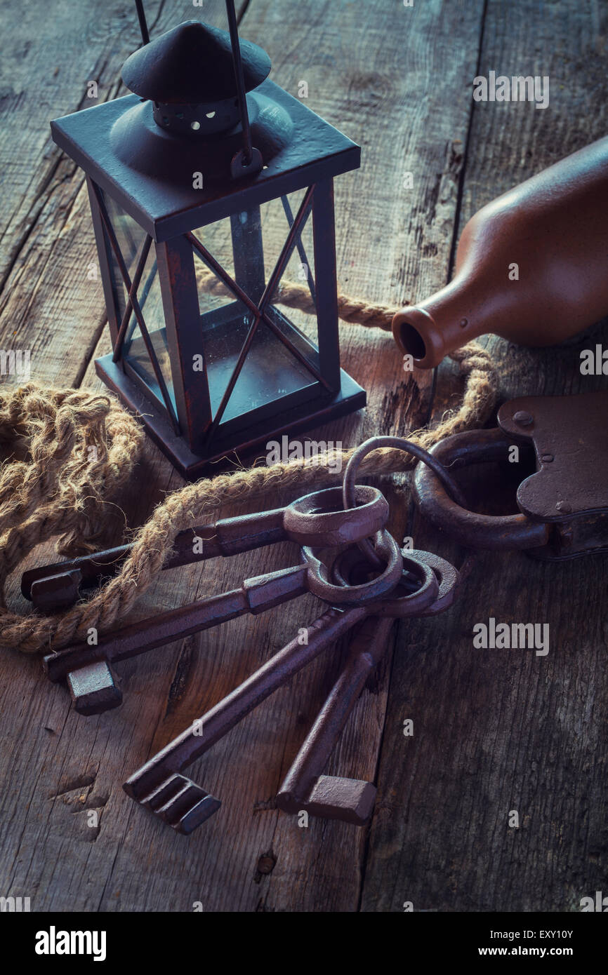 Old rusty lock with keys, vintage lamp, bottle from clay and rope on wooden board. Retro stylized photo. - Stock Image