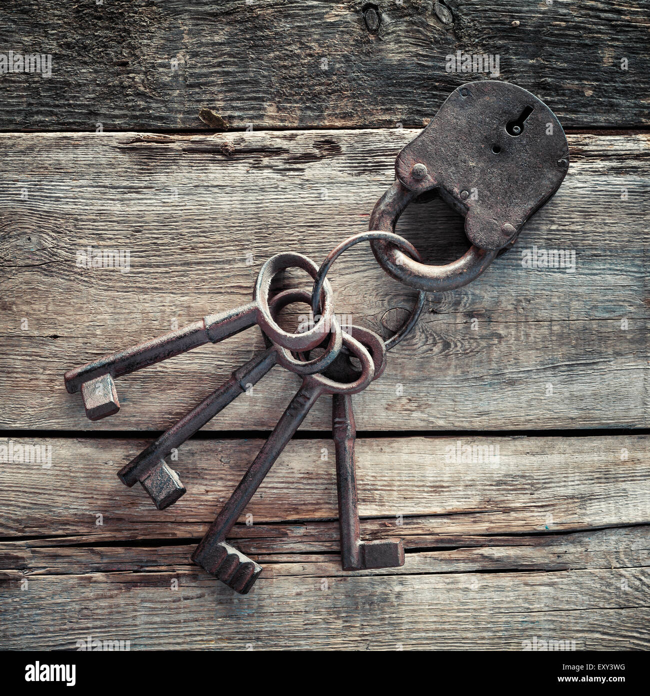Old rusty lock with keys on wooden background. - Stock Image
