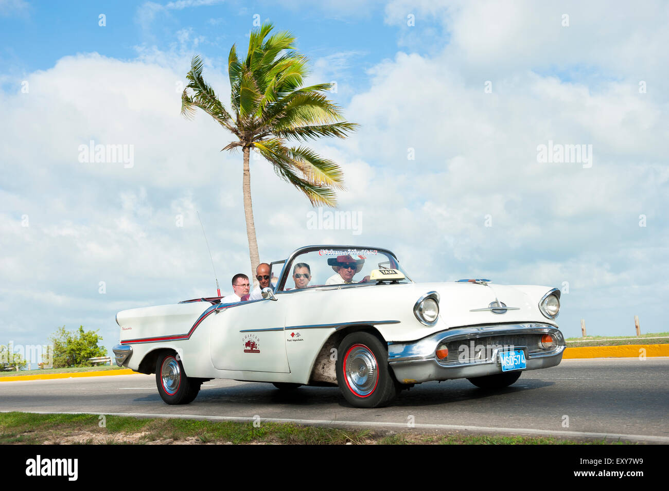 VARADERO, CUBA - JUNE 07, 2011: Tourists ride in white classic vintage American car driving on a coastal road with - Stock Image