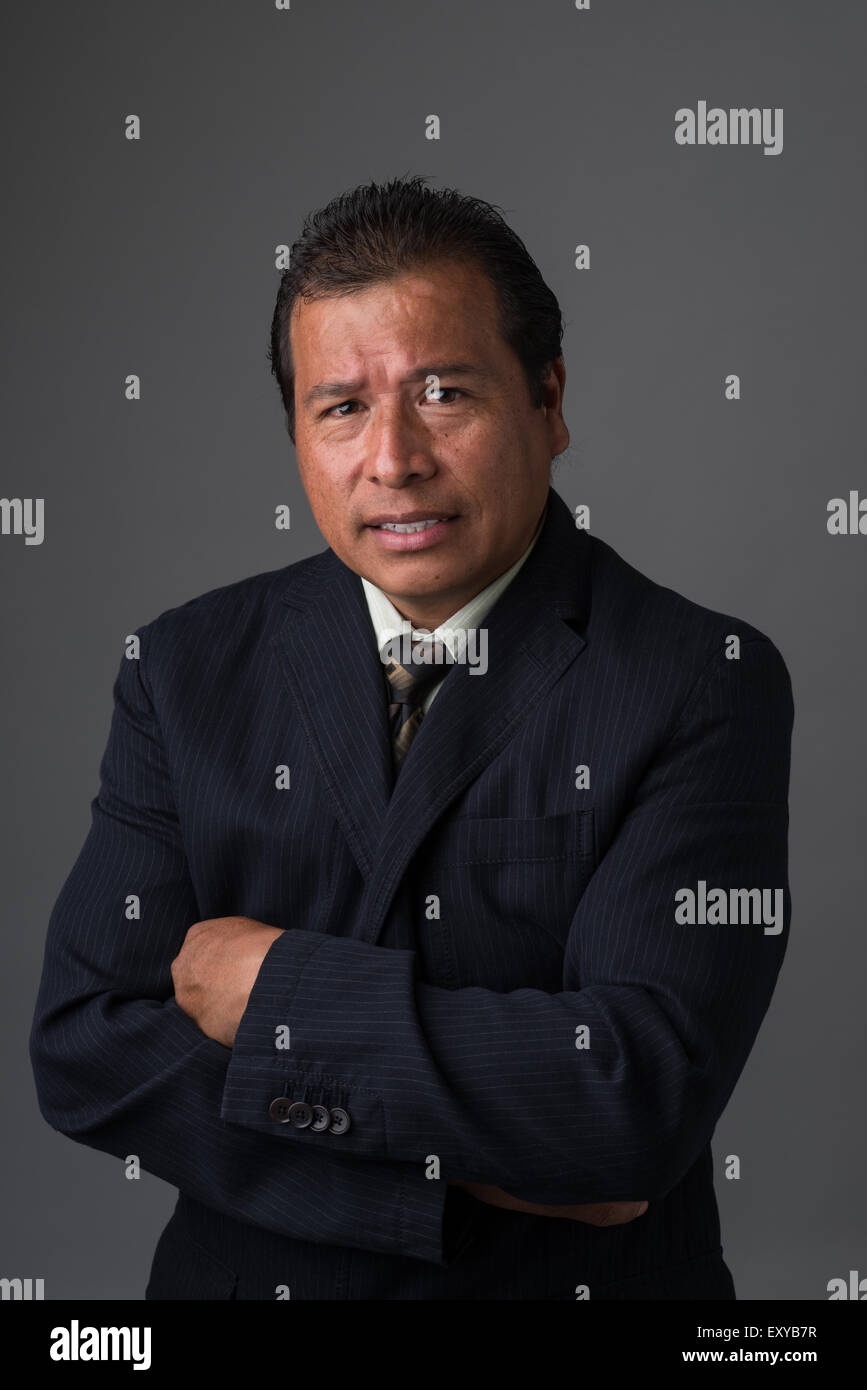 A Hispanic businessman in business suit looking concerned and worried. - Stock Image