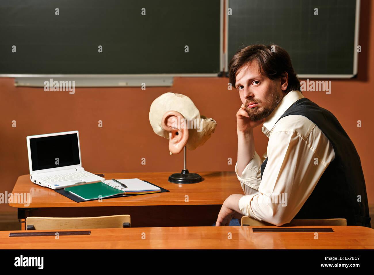Male anatomy teacher sitting at a school desk. Back to school. - Stock Image