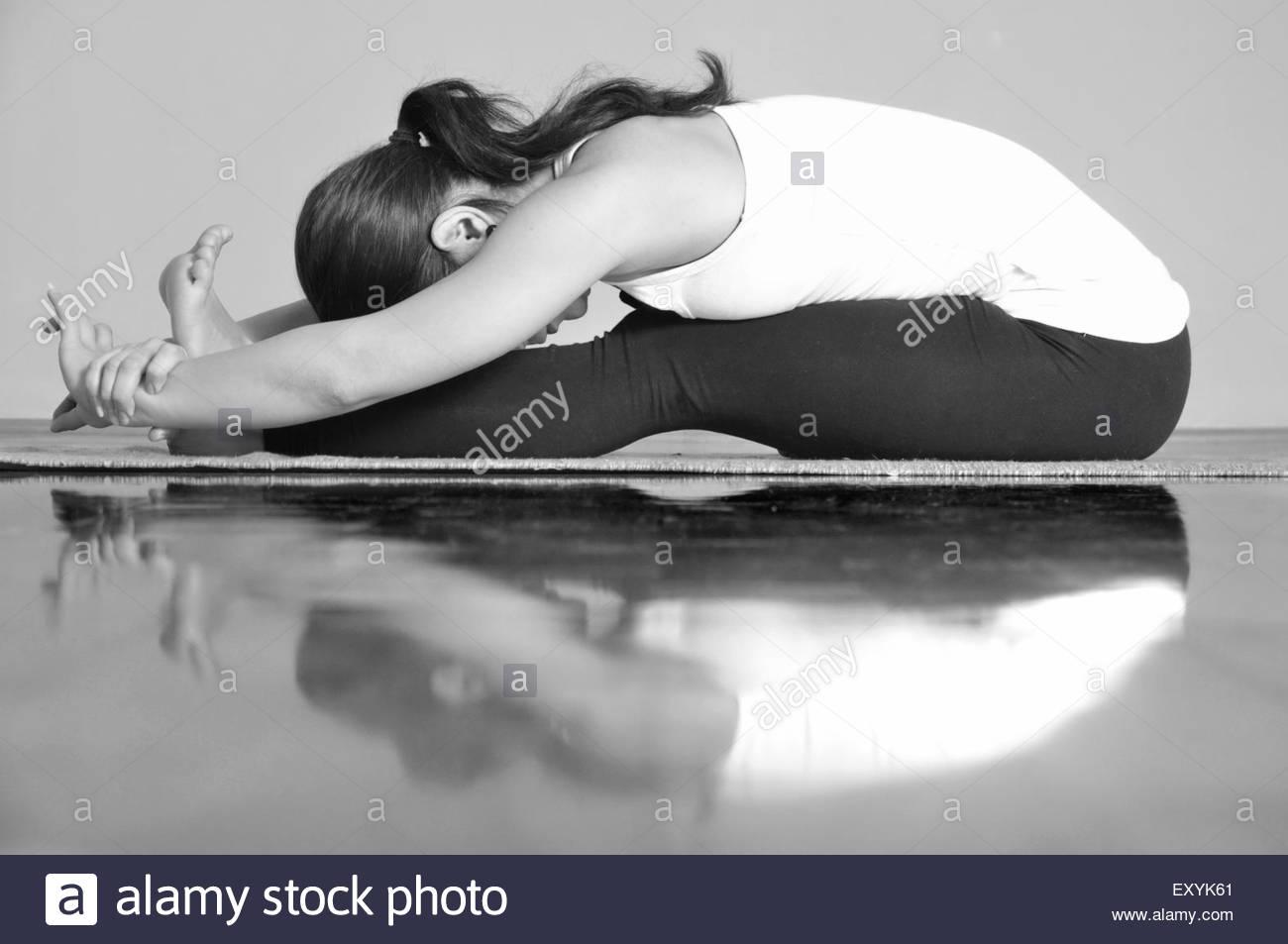 Girl doing Paschimottanasana yoga pose - Stock Image