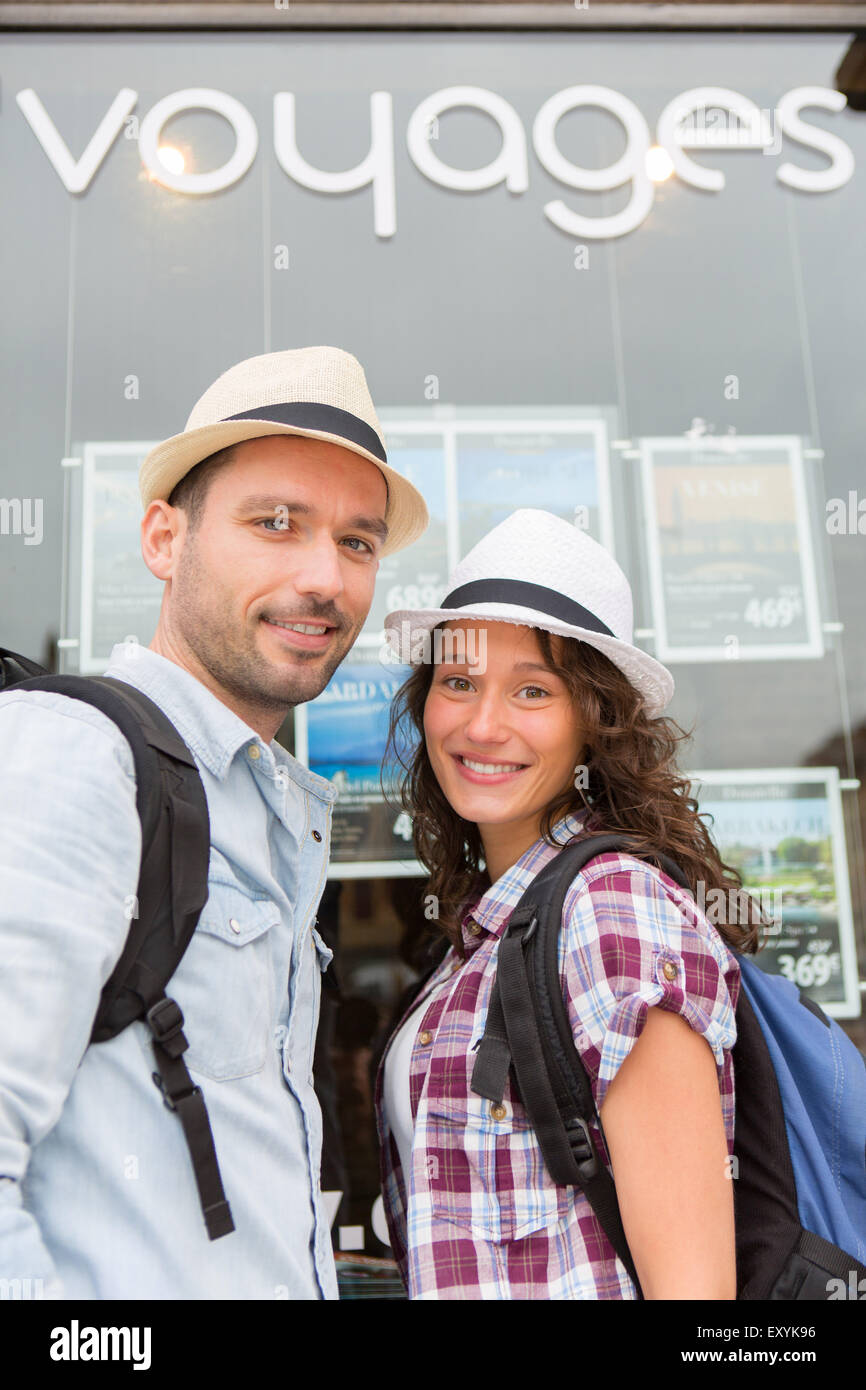 View of a Young happy couple in front of travel agency - Stock Image