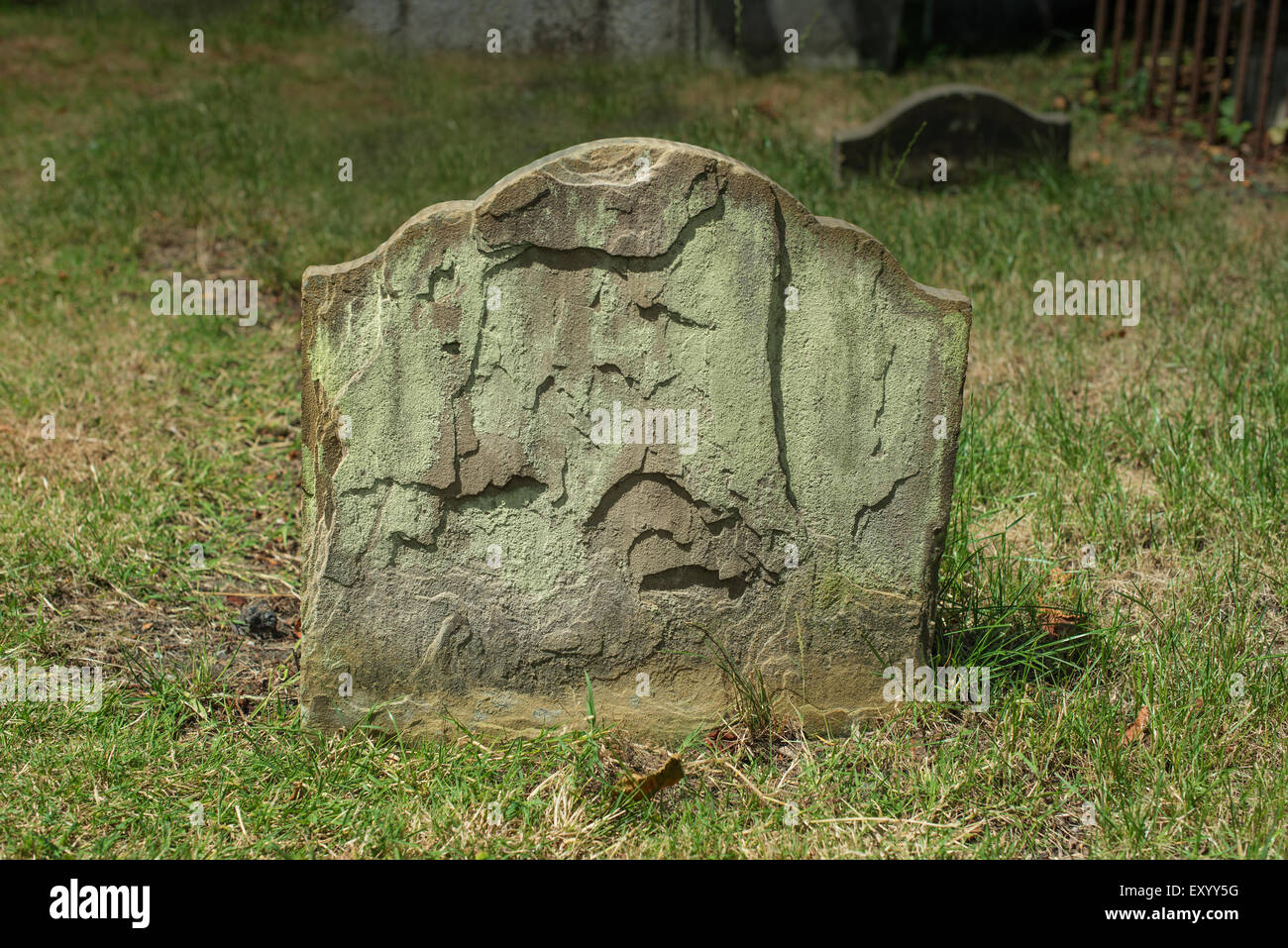 Half buried ancient weathered and flaking gravestone - Stock Image