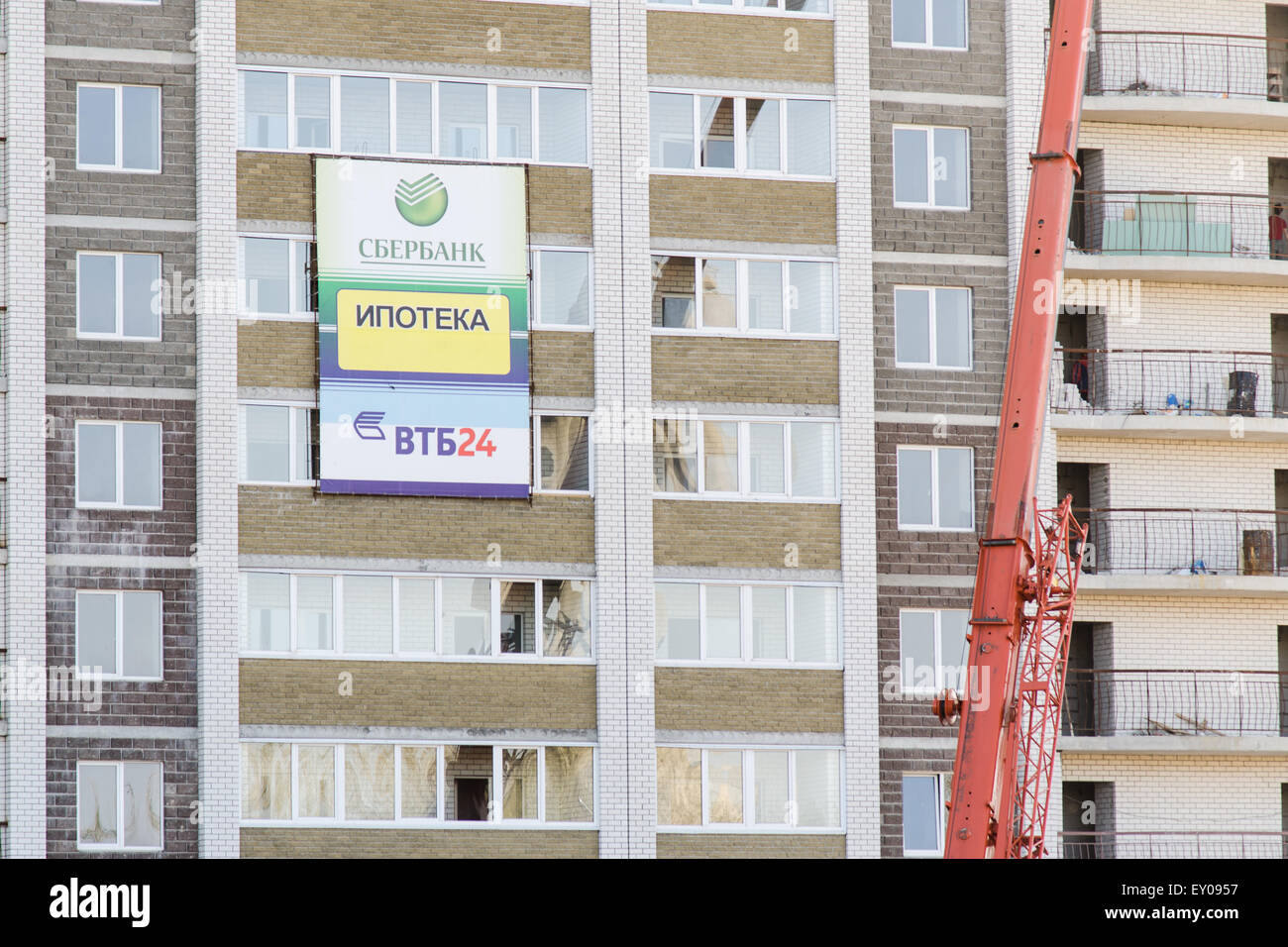 Unfinished multi-storey residential building with an advertising banner mortgage Sberbank, VTB24 on the facade - Stock Image