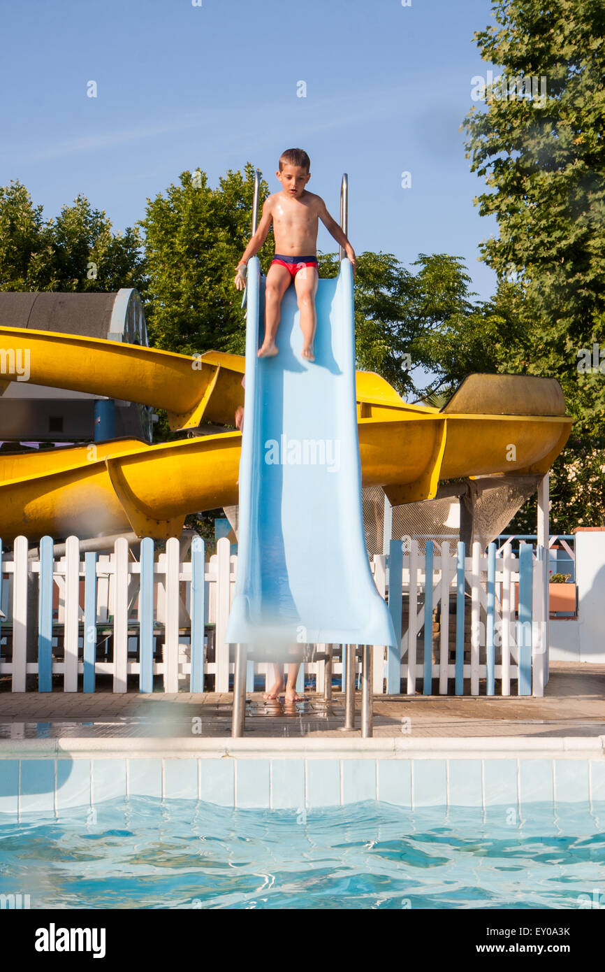 Happy Child Playing With The Slide In The Pool   Stock Image