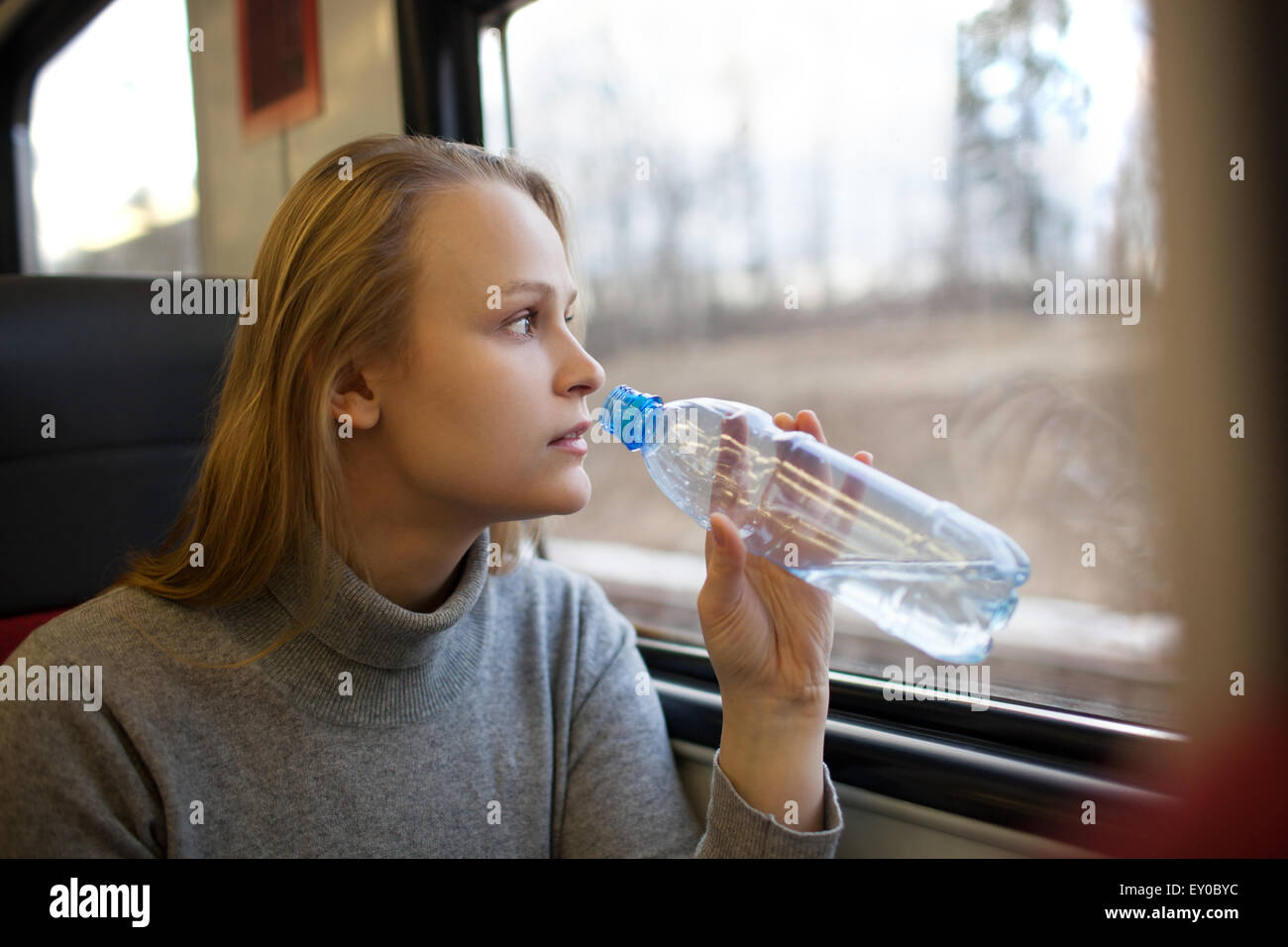 Woman drinking water and looking out train window - Stock Image