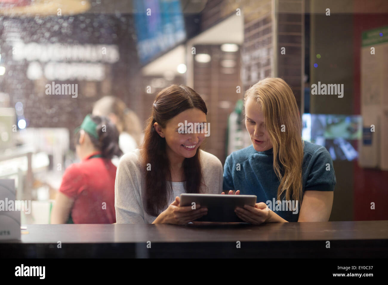 Two women talk cheerfully in the restaurant using electronic tablet - Stock Image