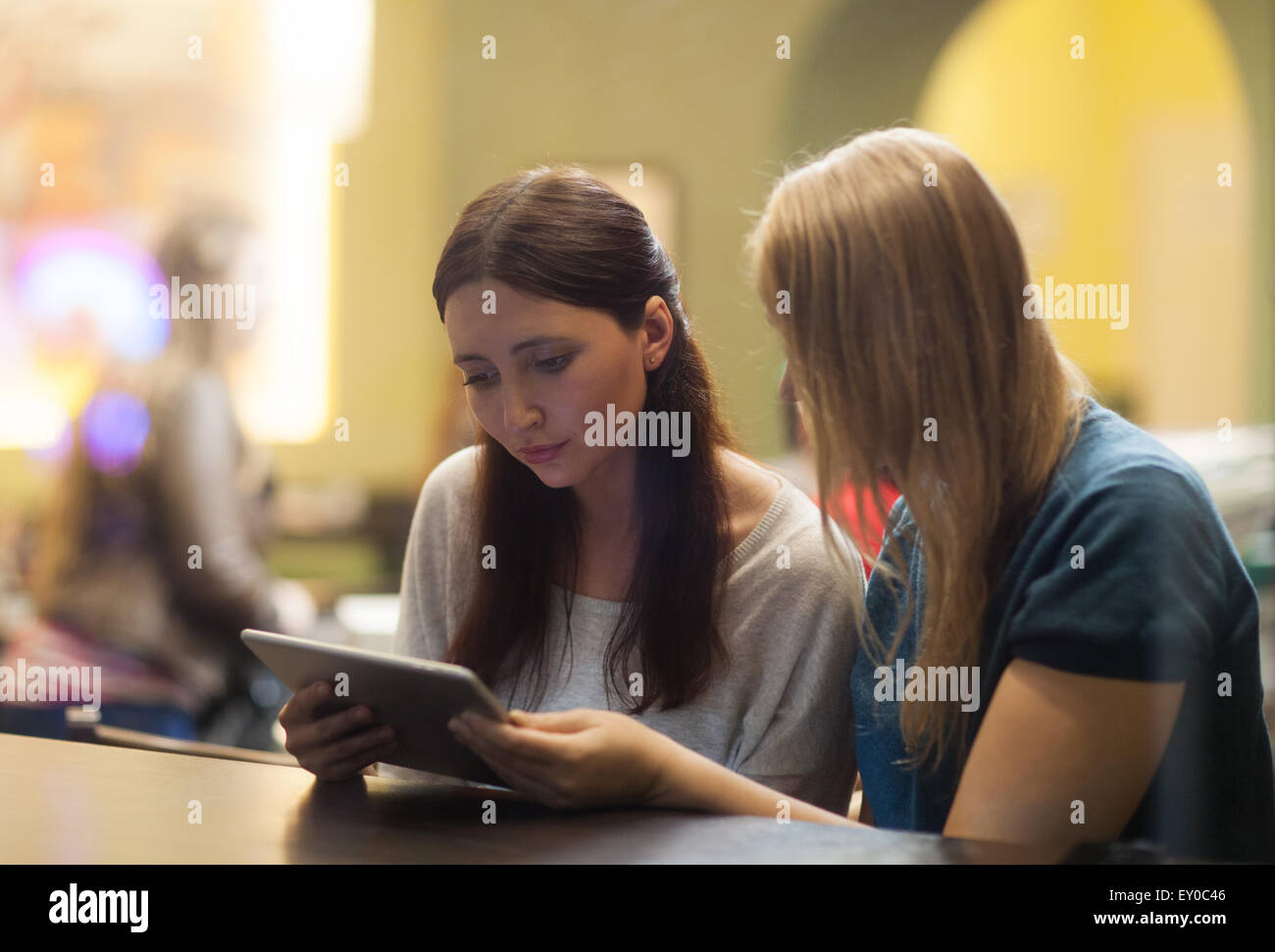 Two women in the restaurant using electronic tablet - Stock Image