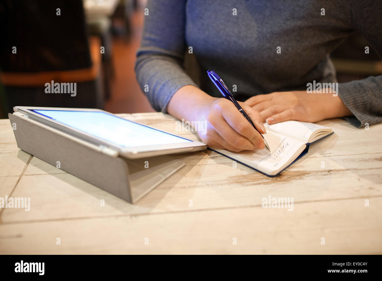 Woman taking down information in notebook - Stock Image