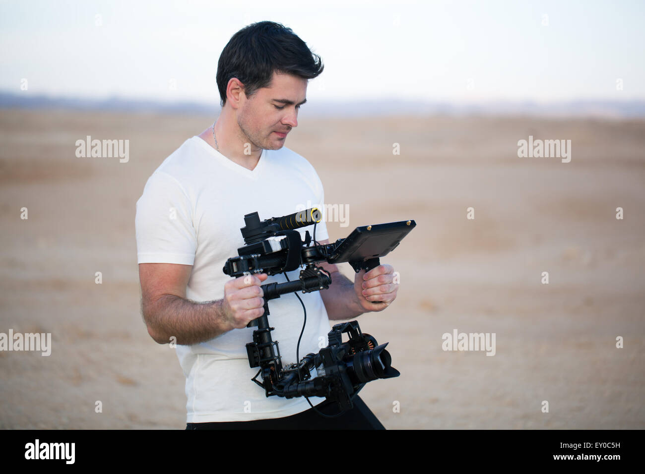 Young man using steadycam for shooting on beach - Stock Image