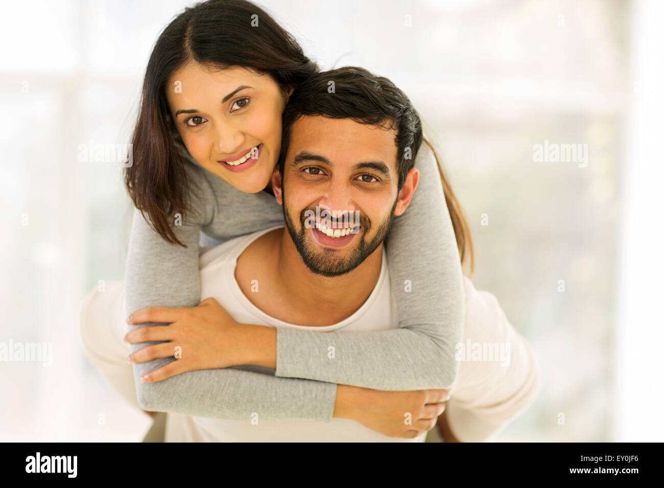 happy young Indian couple having fun with piggyback indoors - Stock Image