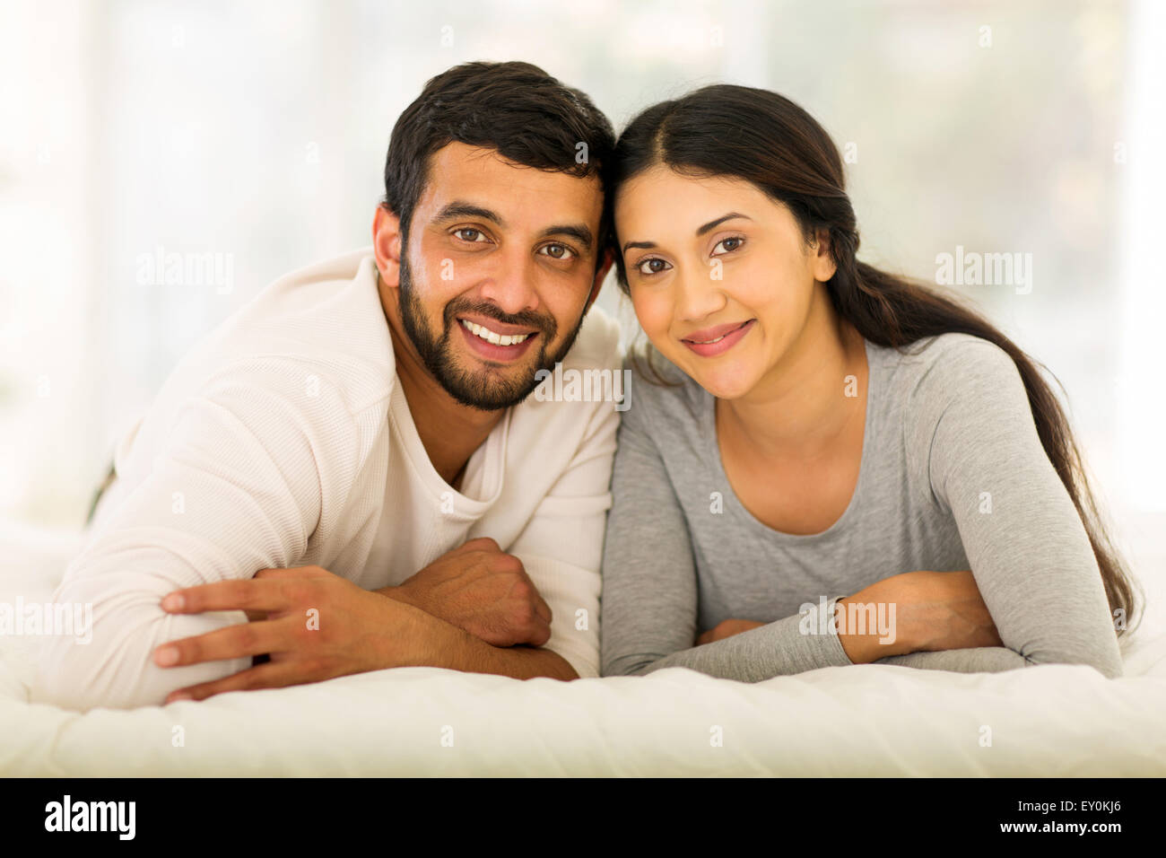 beautiful young Indian married couple lying on bed - Stock Image
