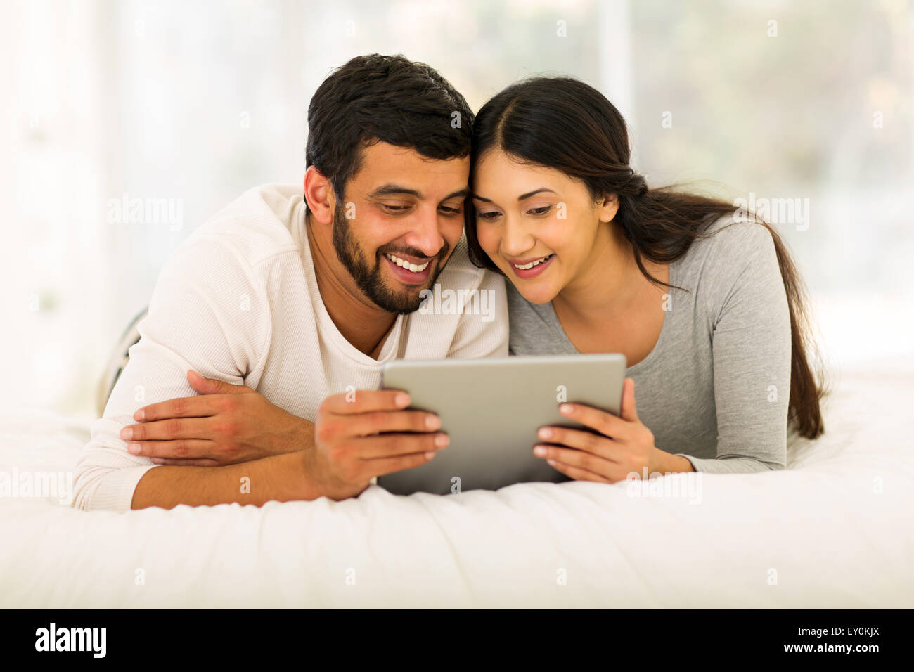 happy young Indian couple lying on bed and using tablet pc at home - Stock Image