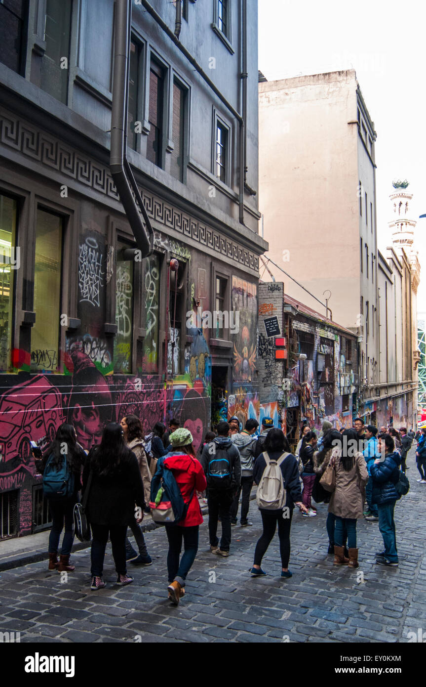 Young tourists admiring the street art displayed in Hosier Lane, Melbourne, Australia - Stock Image