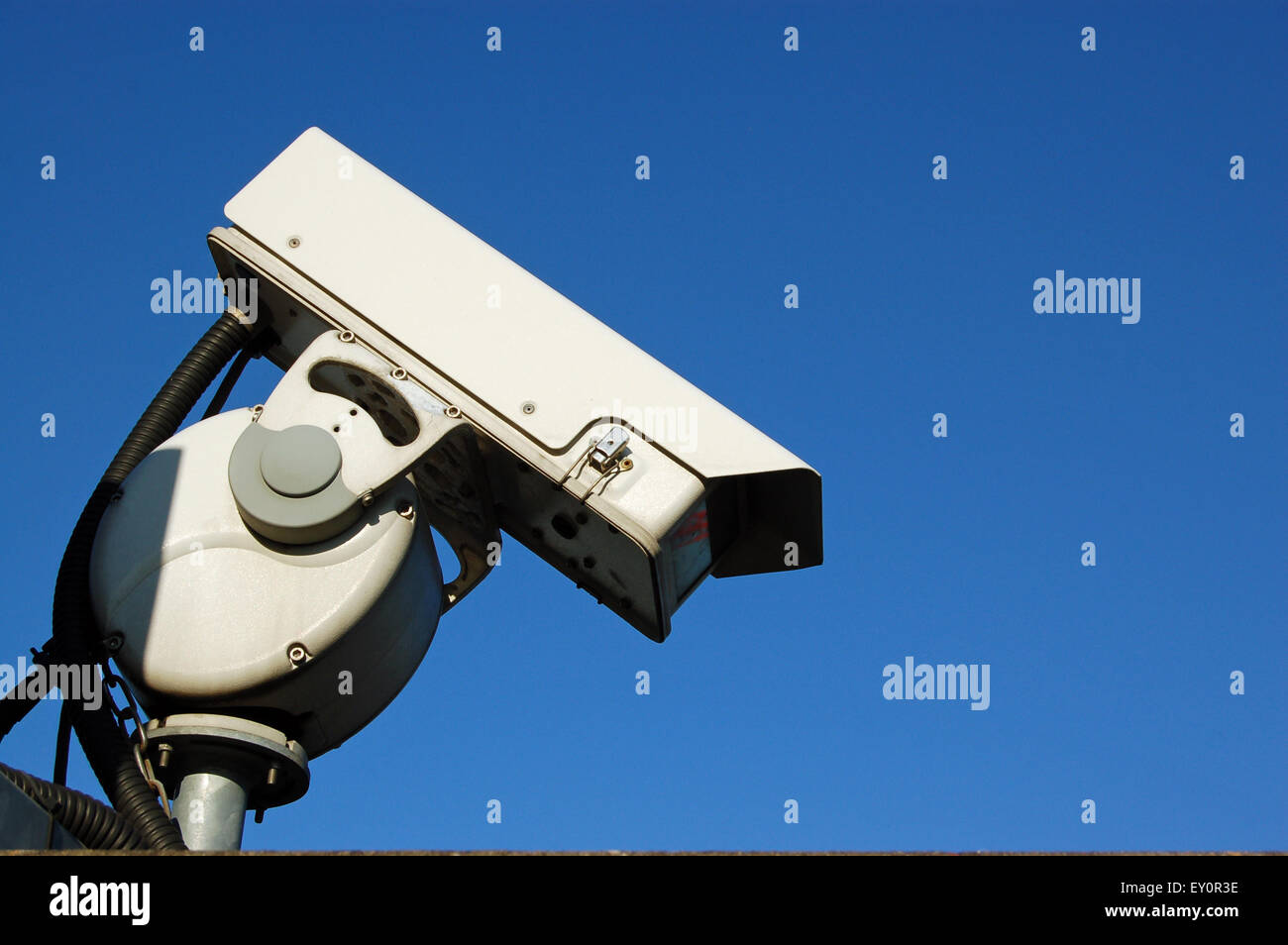A closed circuit security camera photographed against a clear blue sky with space for copy. - Stock Image
