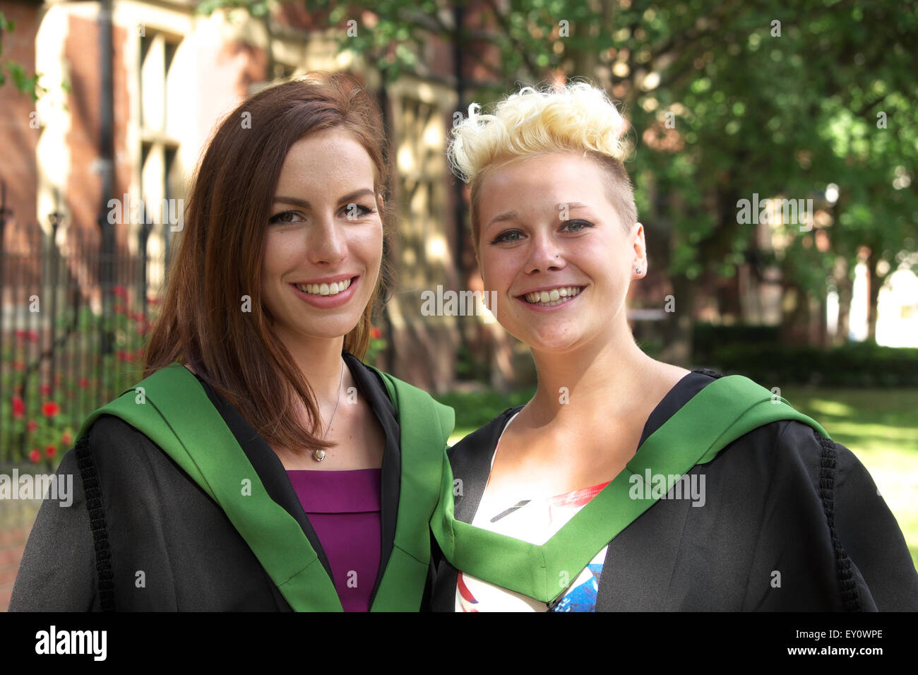 Two Female Graduate Students Wearing Gowns For Their Graduation