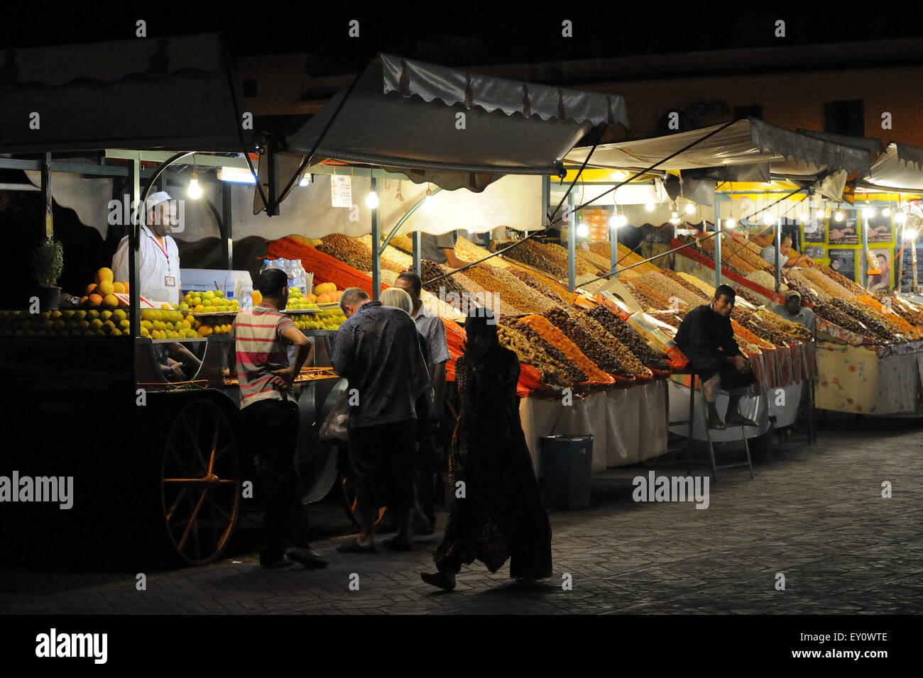 Stands with spices and orange juice stall in Djema el-Fna square at night. Stock Photo