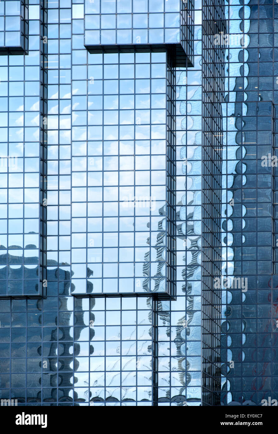 Blue glass wall of a modern skyscraper reflecting other buildings, sky and white clouds - Stock Image