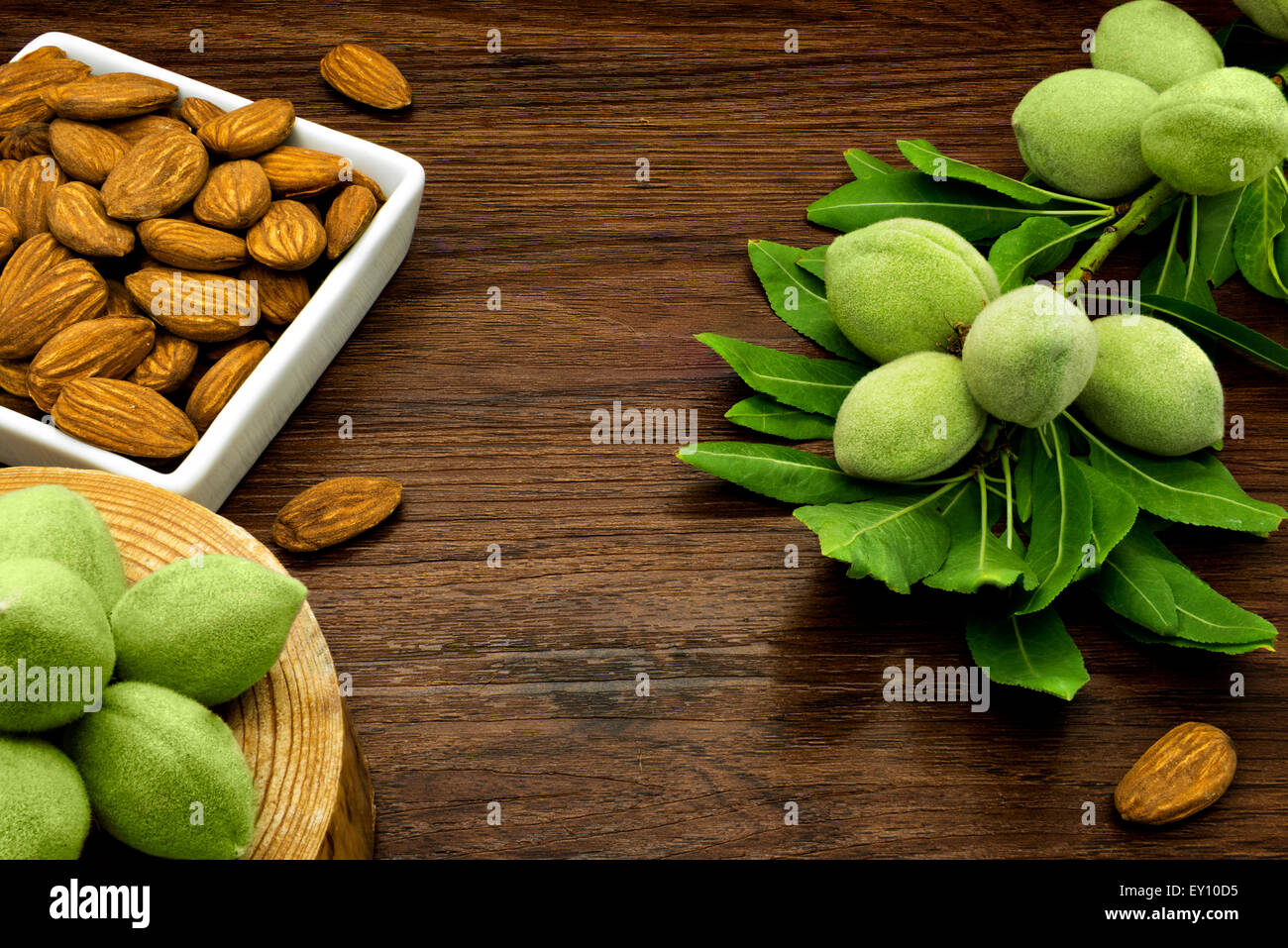 Almond branches and nuts on a wooden table. Stock Photo
