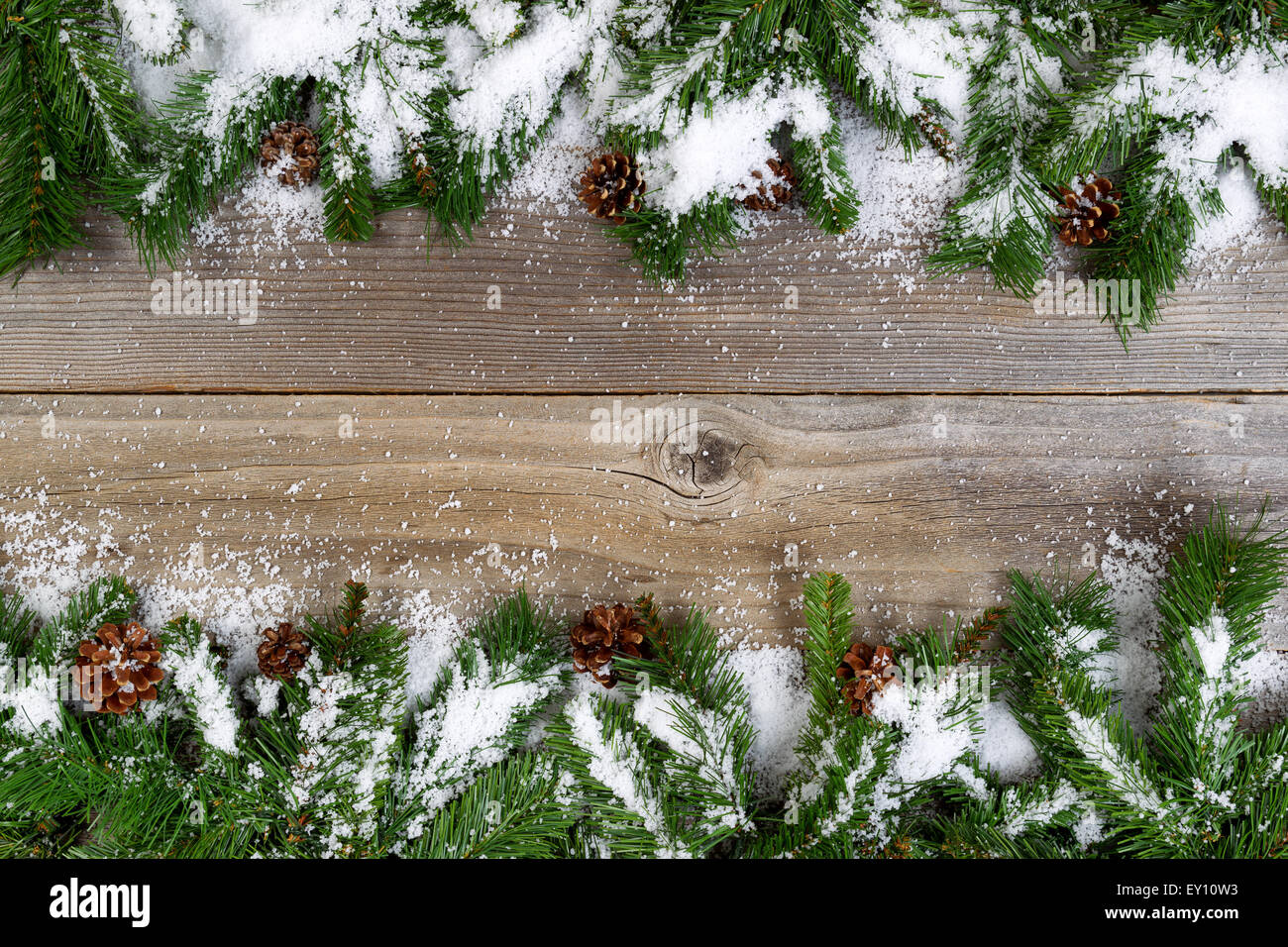 Christmas border, top and bottom of frame, with pine tree branches, cones and snow on rustic wooden boards. Layout Stock Photo