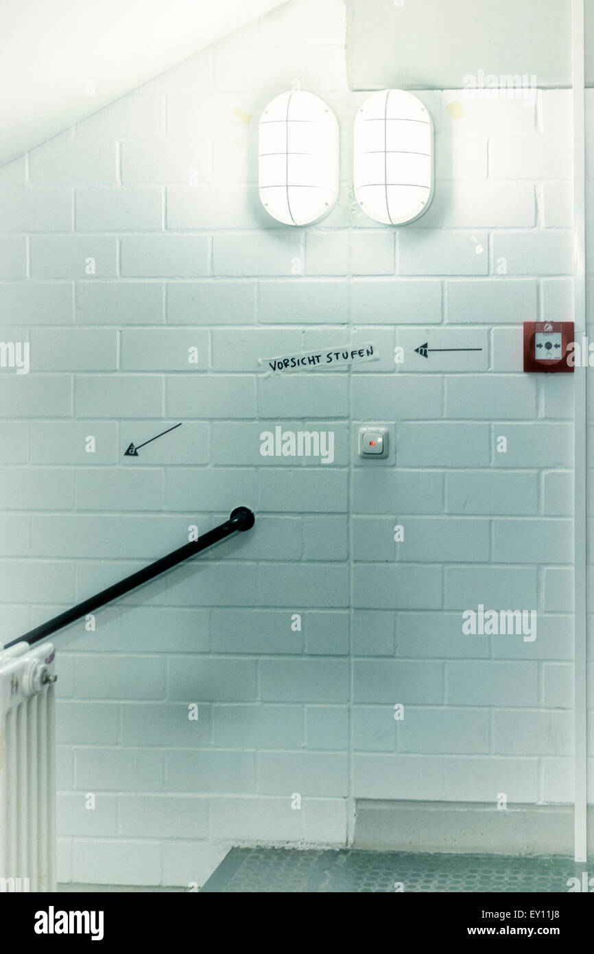 Vorsicht Stufe, Mind the step, Vorsicht stufen with bright lights and painted white wall - Stock Image