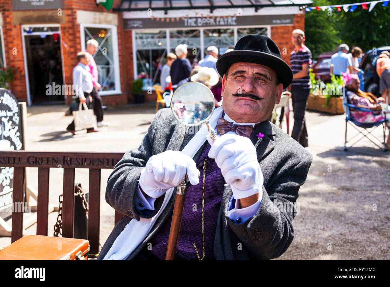 Hercule Poirot investigator with mustache suit using magnifying glass lookalike impersonator - Stock Image