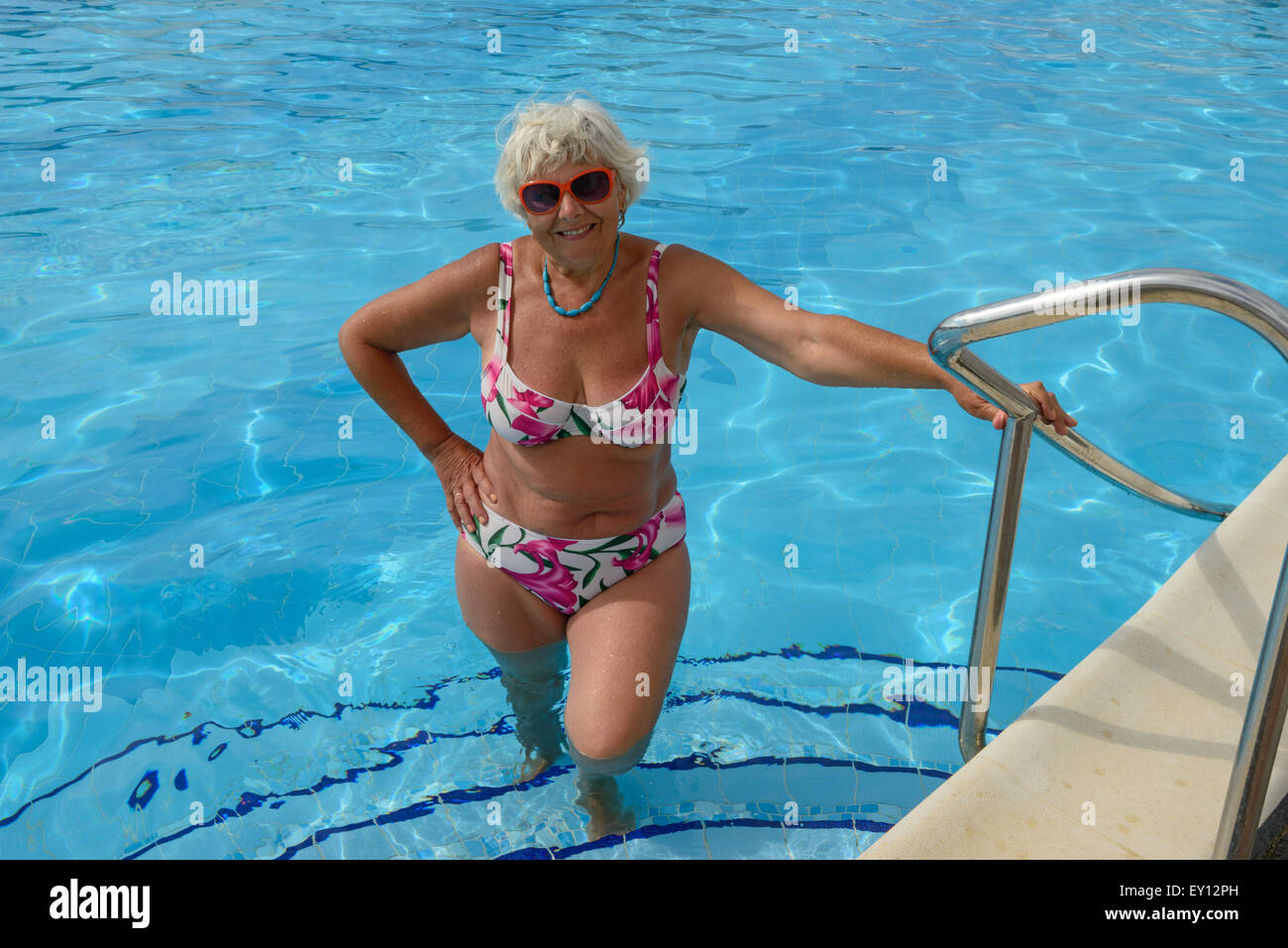 Elderly lady that holds her hand on handrails of swimming ...