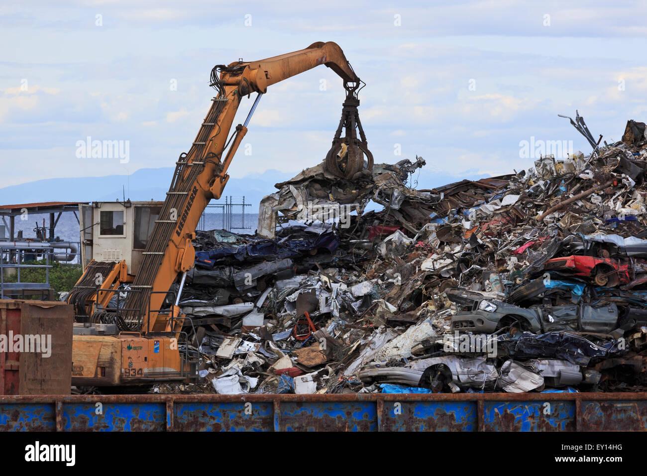 Machine loading scrap metal onto barge, Duke Point, Vancouver Island, British Columbia - Stock Image