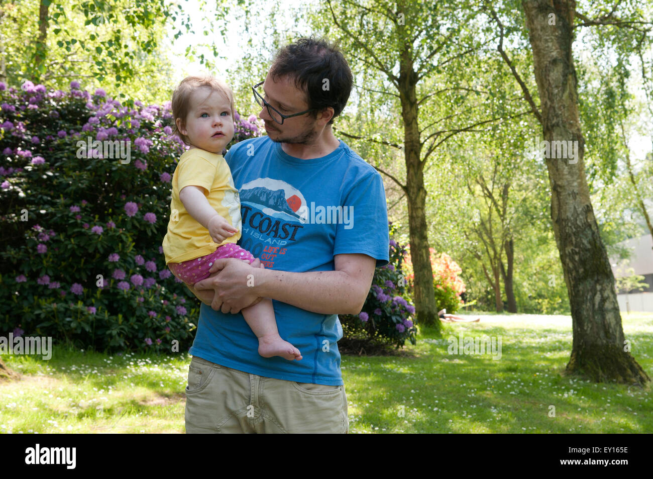 Baby girl being held by her father looking tearful - Stock Image