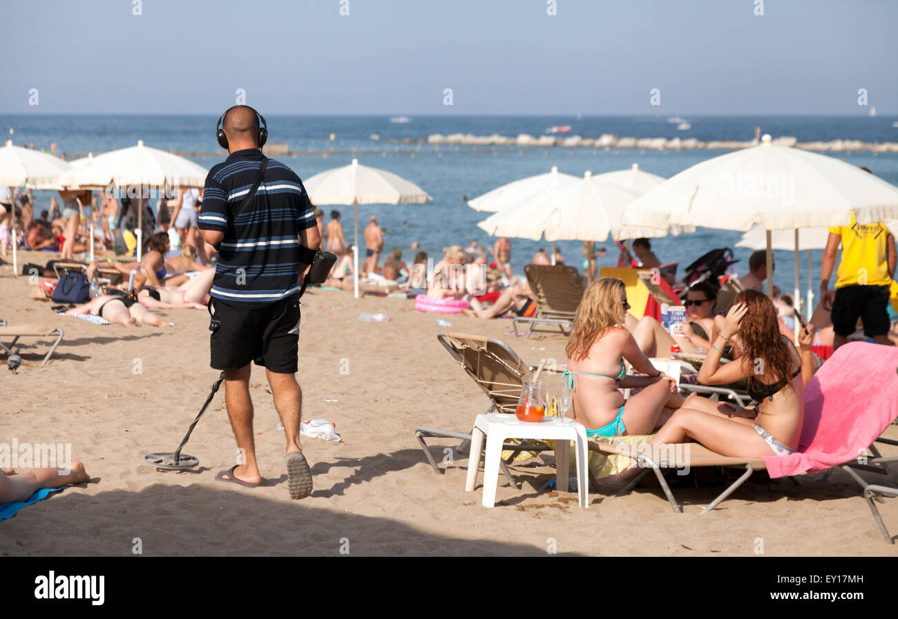 A man metal detecting with a metal detector on the beach, Barceloneta, Barcelona, Spain Europe - Stock Image