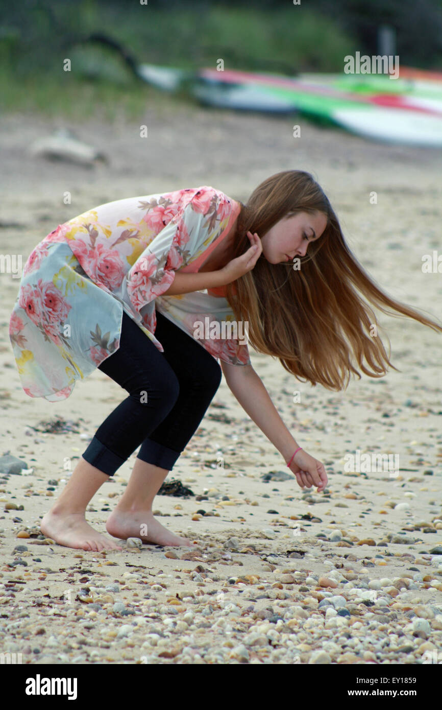 Young Blonde Girl Bending Down Gathering Colorful Stones on Gardiners Bay The Hamptons Long Island New York - Stock Image
