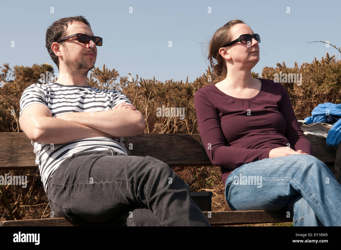 Couple sitting on a bench apart looking annoyed with each other - Stock Image