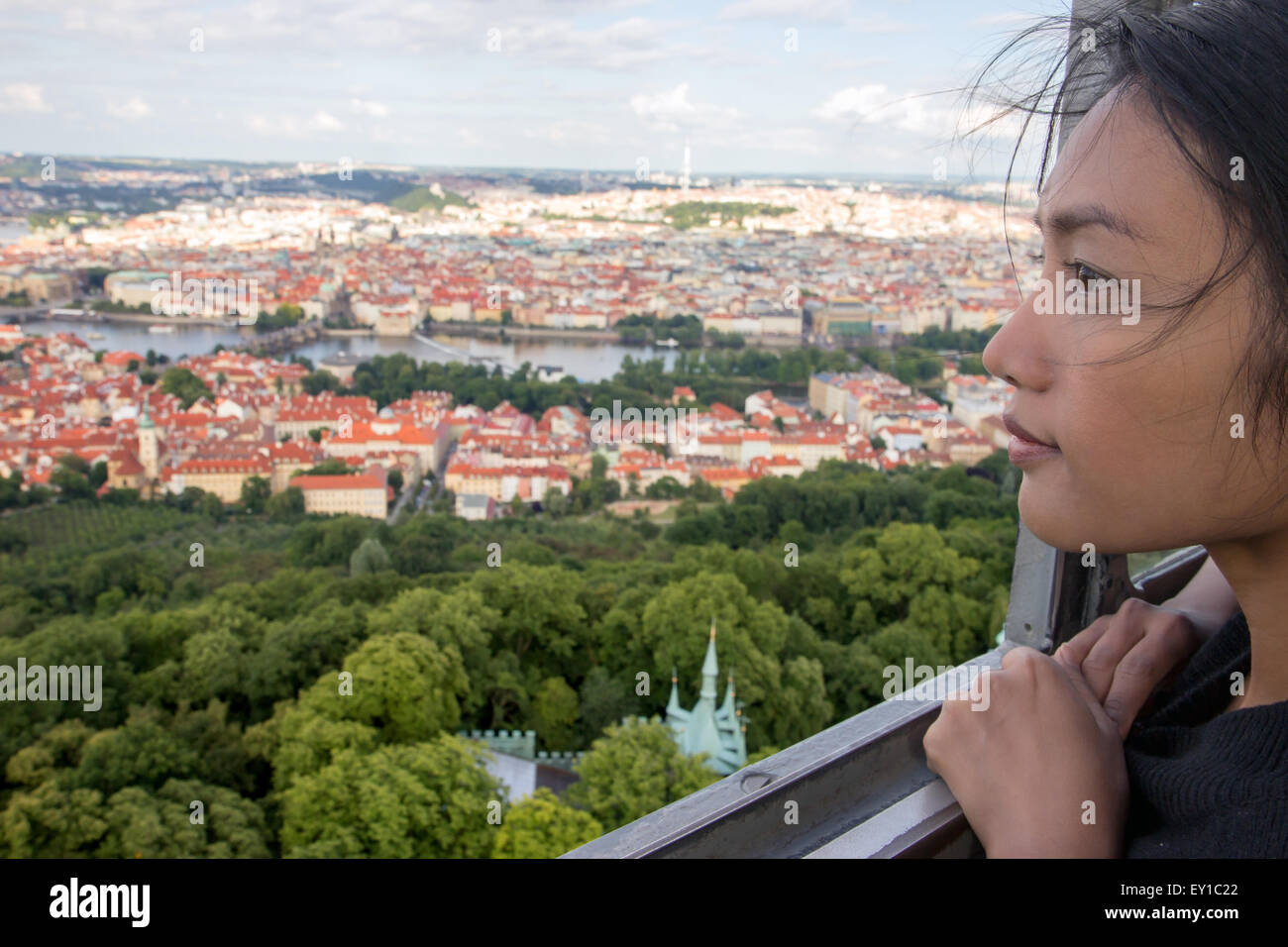 Woman watches cityscape of Prague from outlook tower - Stock Image