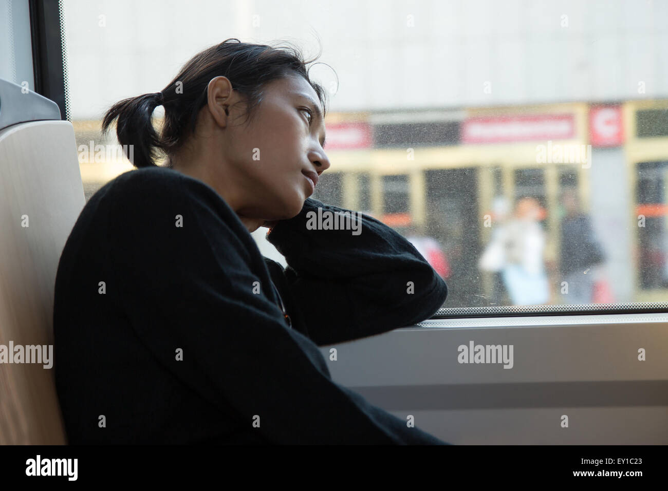 melancholic woman looks out the window of tram - Stock Image