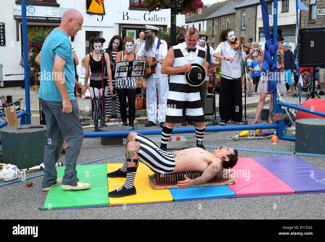 A traditional fairground strongman laying on a bed of nails during a street performance by the '  Swamp Circus - Stock Image