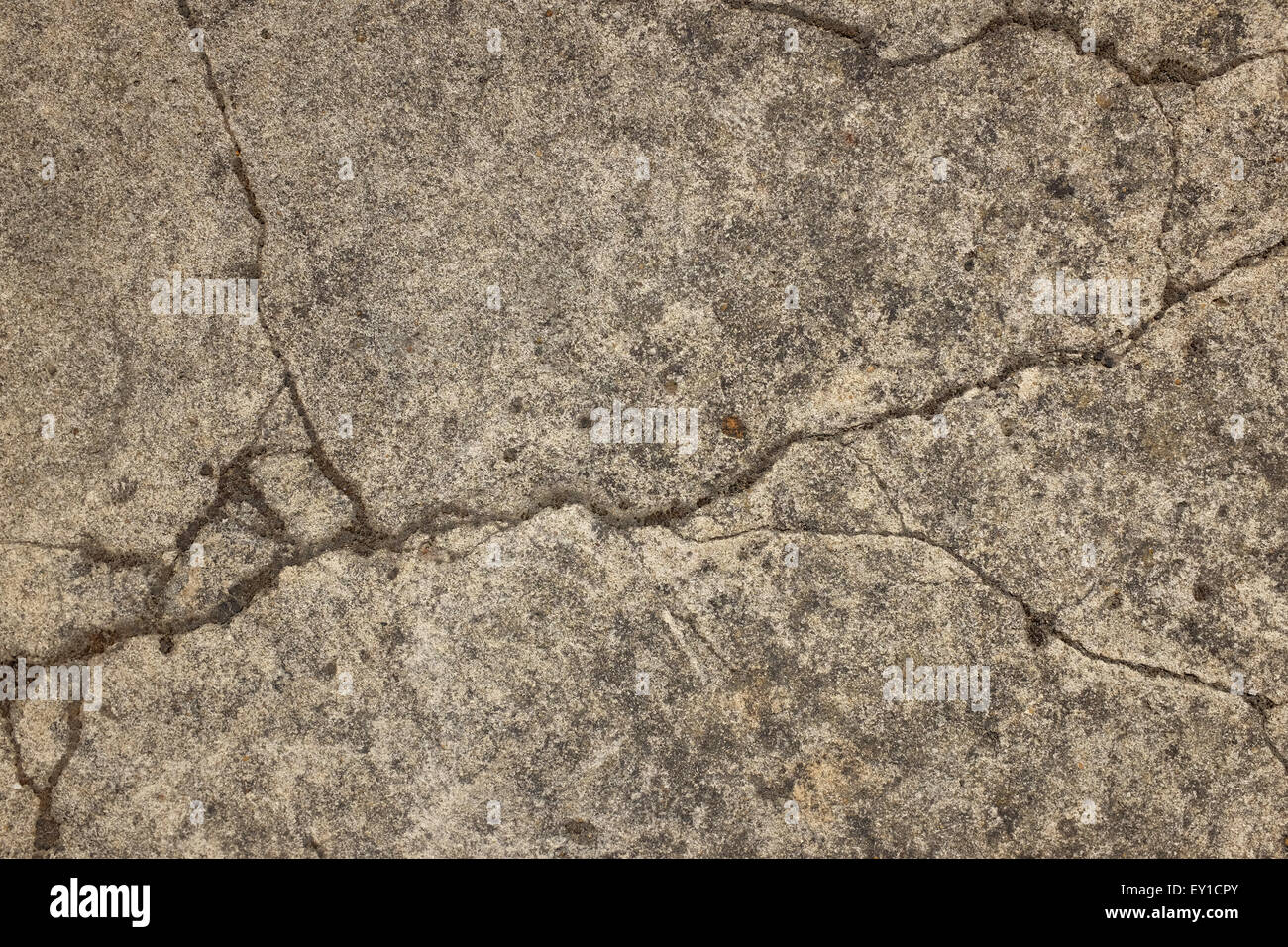 Cracked and weathered concrete surface as an abstract background texture - Stock Image