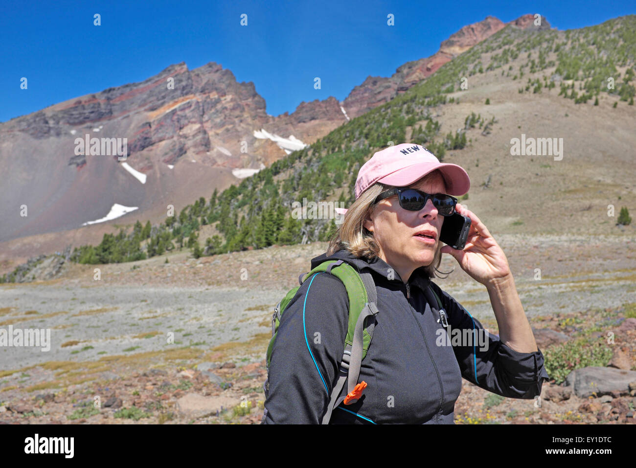 A female hiker in the wilderness talking to someone on her cell phone. - Stock Image