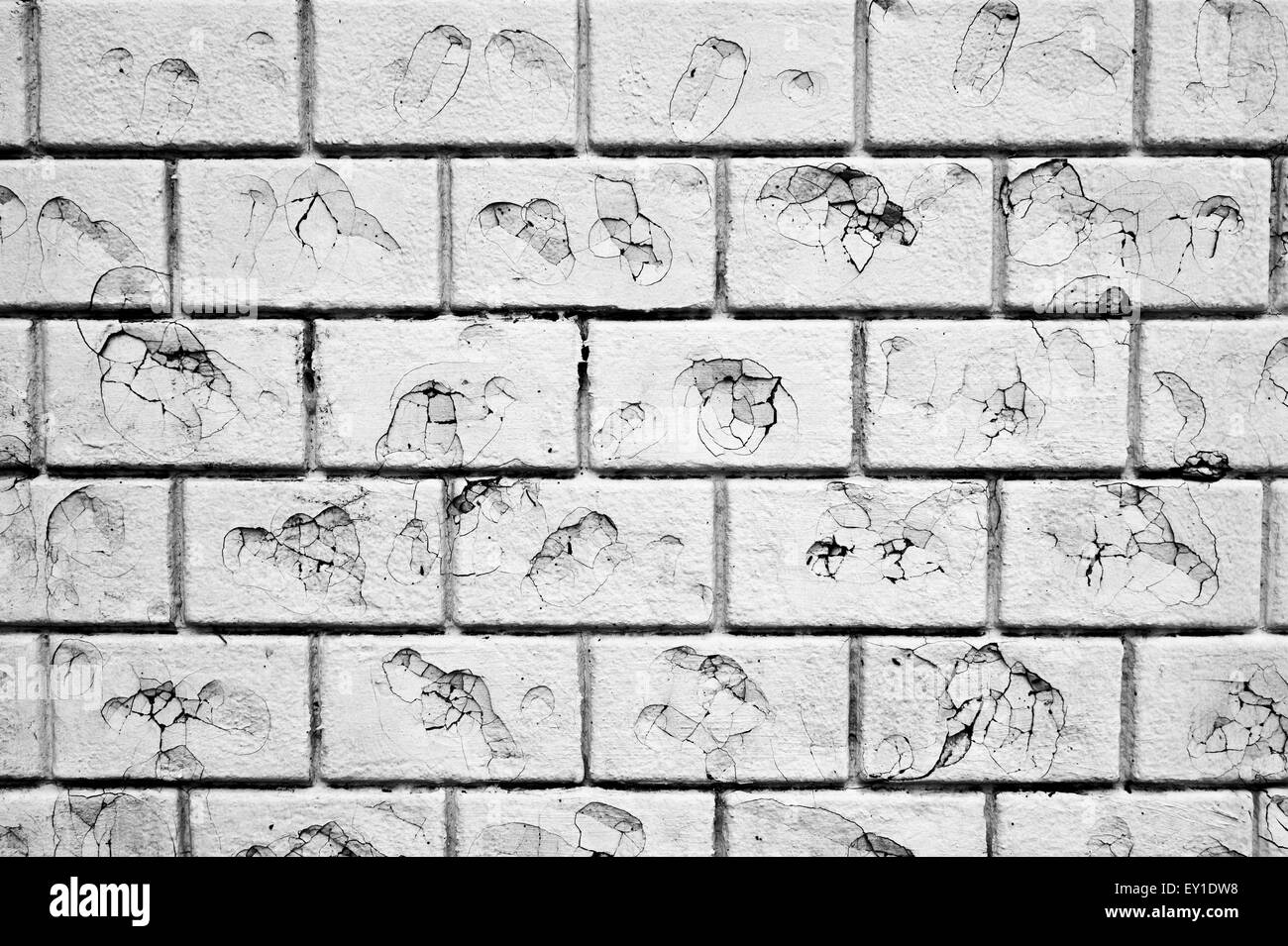 Part of a white brick wall with damage, possibly by bullets Stock Photo