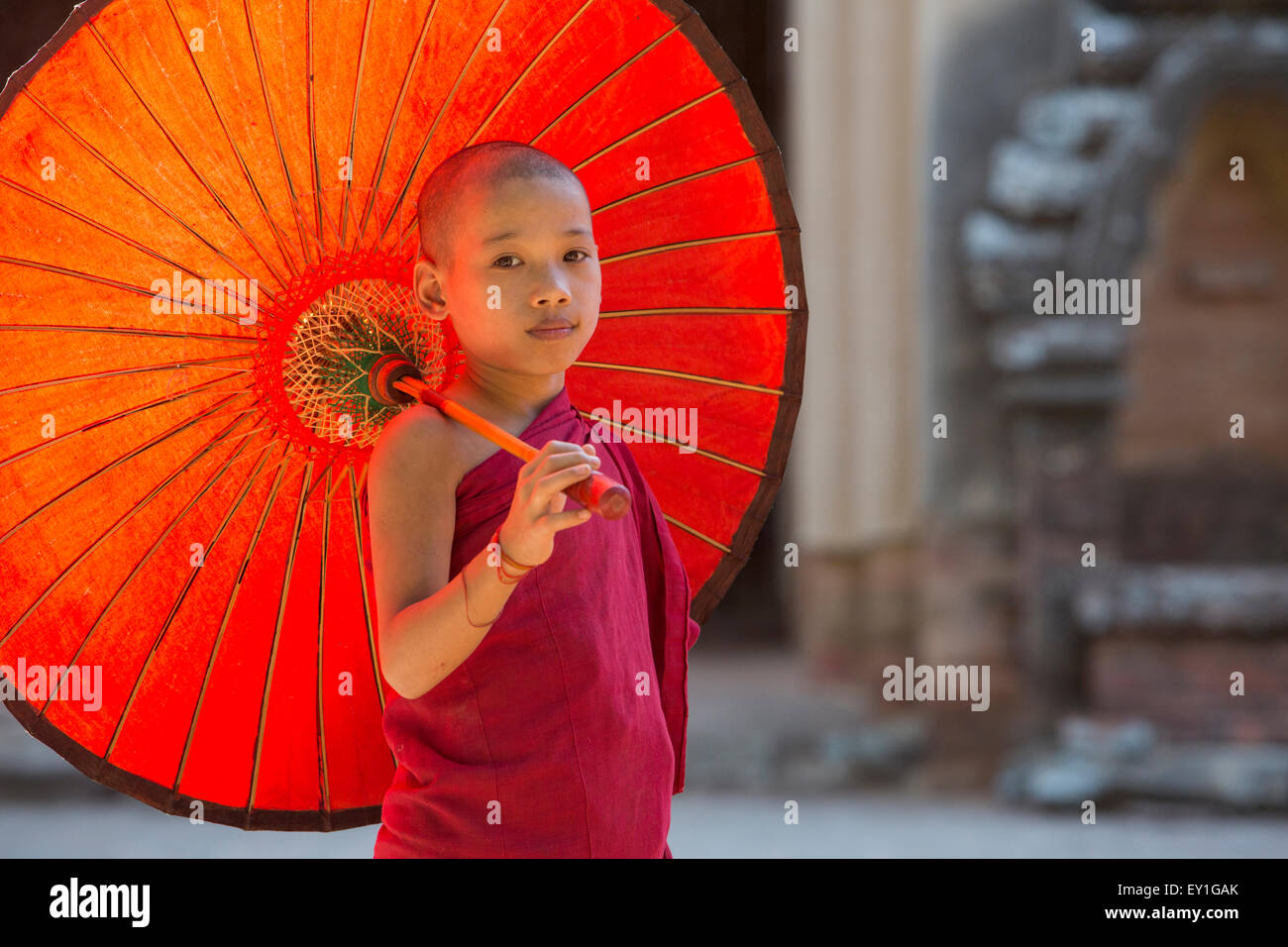 Buddhist novice monk holding umbrella at entrance to Sulamani Temple, Myanmar Stock Photo