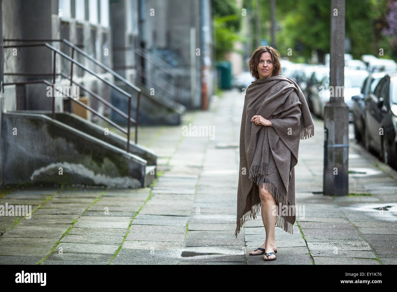 Young attractive woman in a poncho standing in the street near the house. - Stock Image