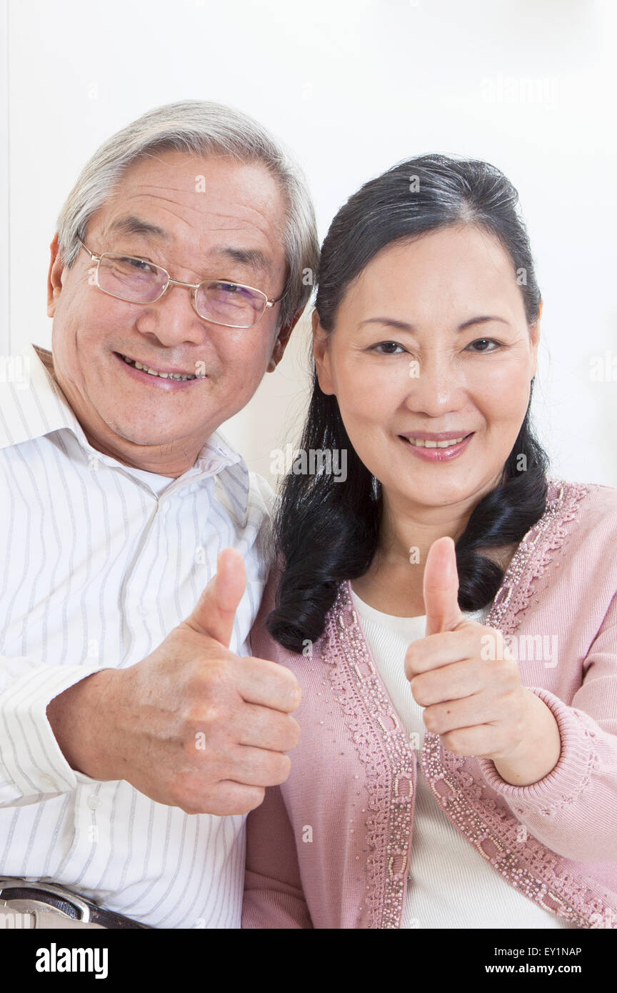 Senior couple smiling at the camera with thumbs up, - Stock Image