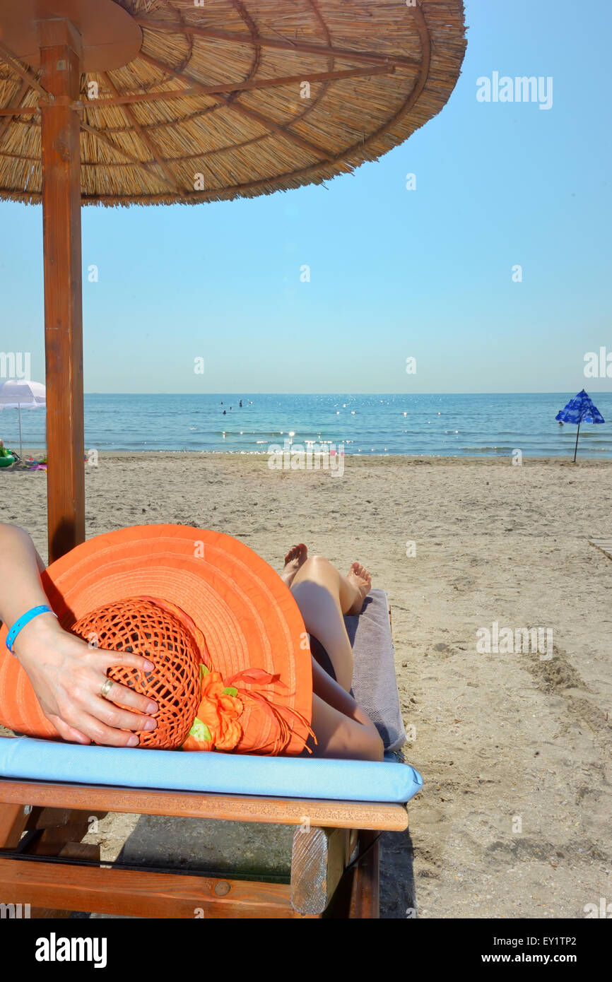 woman relaxing on sunbed on beach - Stock Image