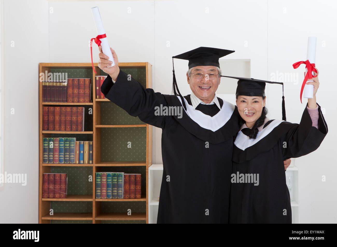 Senior Couple Wearing Graduation Gown Stock Photos & Senior Couple ...