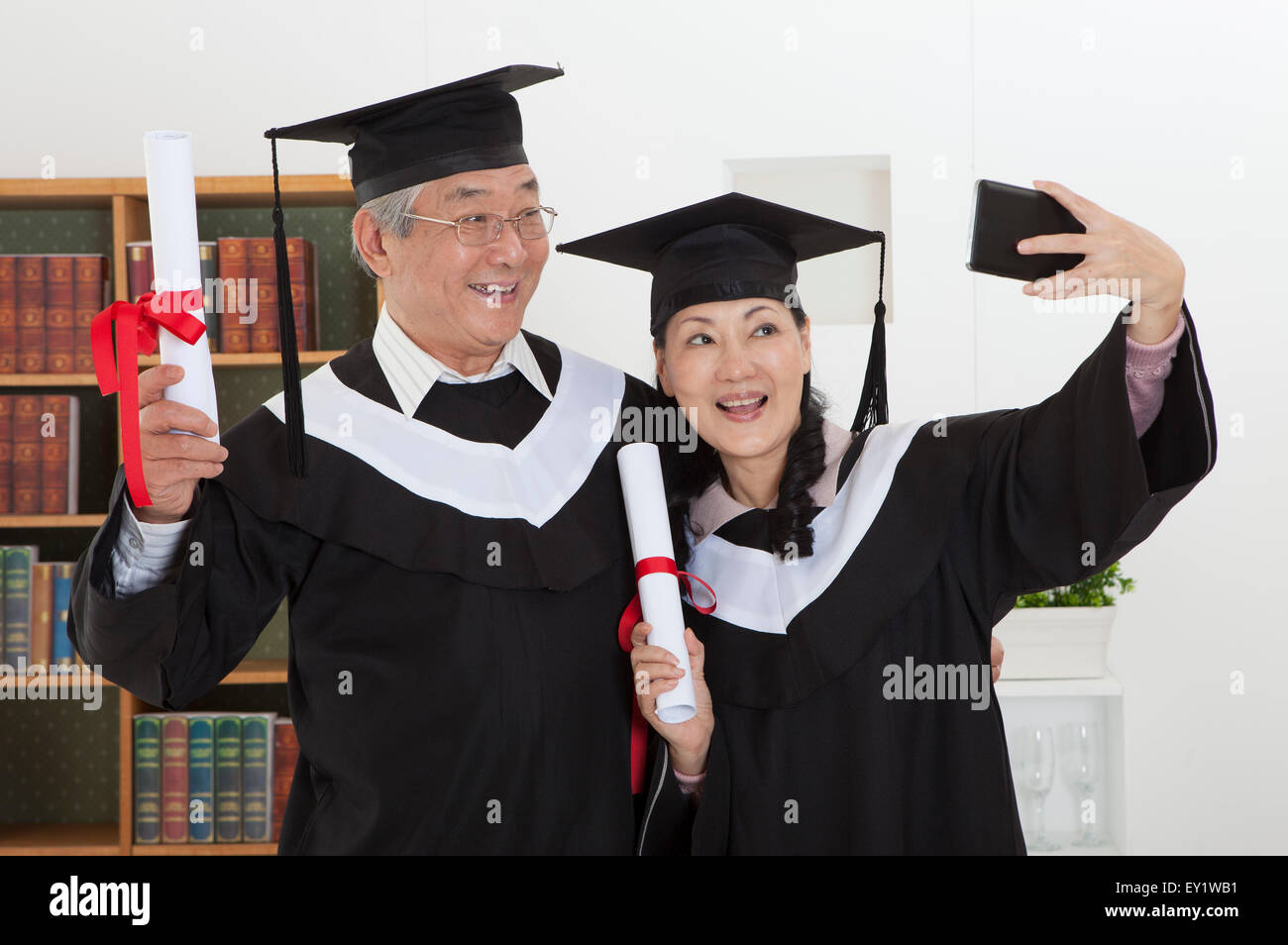 Senior couple wearing graduation gown and holding diploma with smile ...