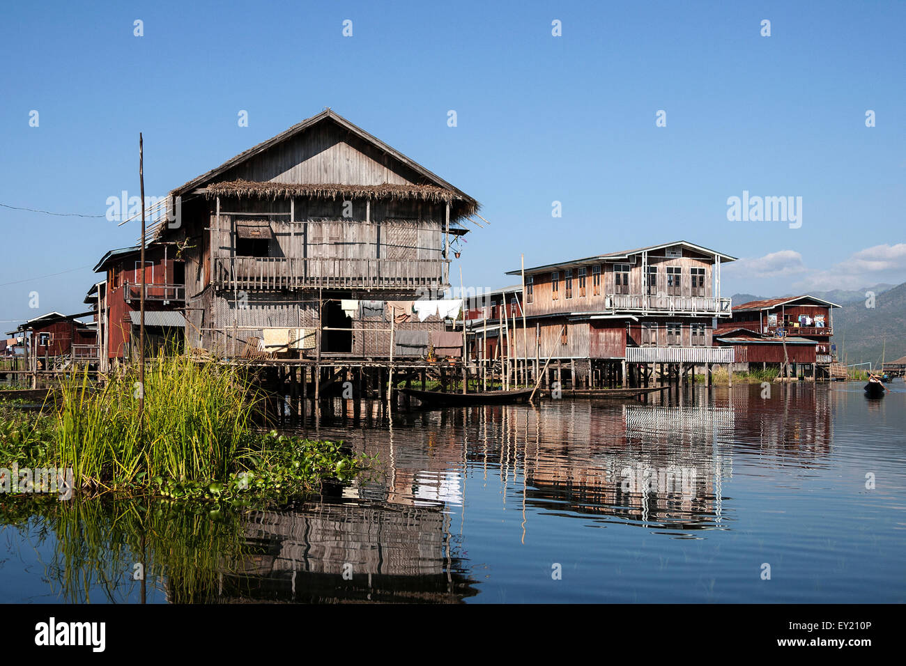 Traditional stilt houses in Inle Lake, reflection in the water, Shan State, Myanmar - Stock Image