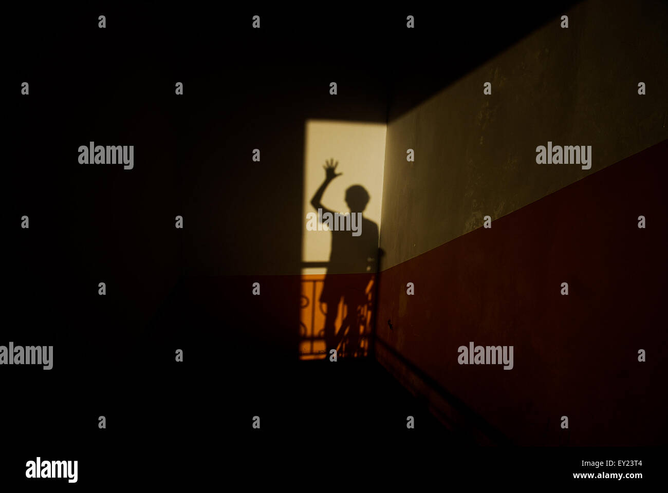 Shadow of a man projected on the wall. - Stock Image